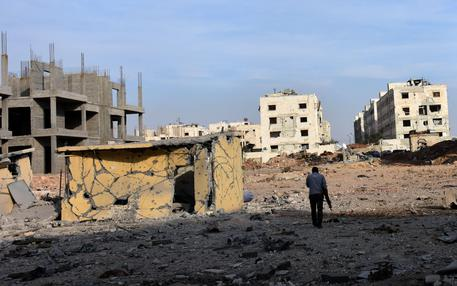 epa05623259 Armed man walk through rubble after liberating the area 1070 apartment in Aleppo province, Syria, 08 November 2016. According to media the Syrian army's control over the project in 1070 an apartment south-west city of Aleppo after fierce battles, by Syrian forces against the al-Father Army forces, where Syrian army heading for control of the Al Hekmeh and the Al-rashidine area and suburb Assad School.  EPA/STR