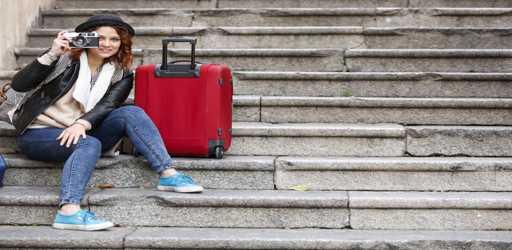 Giovane turista seduta in una scala con la valigia rossa ci guarda con la reflex in mano