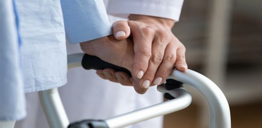 Physiotherapist,Touches,Disabled,Elderly,Woman,Hand,While,She,Holding,Walking